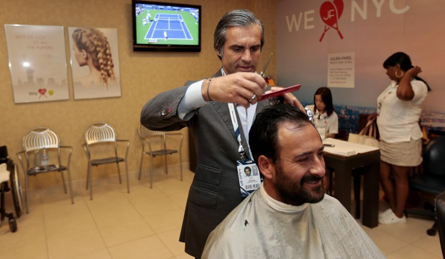 In this photo taken on Wednesday, Sept. 3, 2014, Julien Farel trims the hair of wheelchair tennis player Michael Jeremiasz at the hair salon for players inside Arthur Ashe Stadium at the Billie Jean King National Tennis Center during the 2014 U.S. Open tennis tournament in New York. For eight straight U.S. Opens, Farel has been the tournament's official hairstylist, operating the pop-up salon in the inner sanctum of Arthur Ashe Stadium that offers manicures, pedicures, makeup and, of course, cuts, styles and braids for every participant in the tournament, free of charge. (AP Photo/Julio Cortez)