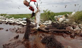 FILE- In this June 4, 2010 file photo, a worker picks up blobs of oil with absorbent snare on Queen Bess Island at the mouth of Barataria Bay near the Gulf of Mexico in Plaquemines Parish, La. U.S. District Judge Carl Barbier ruled Thursday, Sept. 4, 2014, in New Orleans, La., that BP acted recklessly and bears most of the responsibility for the oil spill. The ruling exposes BP to about $18 million in civil fines under the Clean Water Act.  (AP Photo/Gerald Herbert, File)