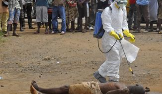 A health worker sprays the body of a man who is suspected of dying due to the Ebola virus with disinfectant chemicals  in Monrovia, Liberia, Thursday, Sept. 4, 2014. As West Africa struggles to contain the biggest ever outbreak of Ebola, some experts say an unusual but simple treatment might help: the blood of survivors. The evidence is mixed for using infection-fighting antibodies from survivors' blood for Ebola, but without any licensed drugs or vaccines for the deadly disease, some say it's worth a shot. (AP Photo/Abbas Dulleh)