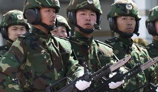 Soldiers from the People's Liberation Army (PLA) 6th Armored Division carry the Chinese type 97 semiautomatic machine guns at their military base on the outskirts of Beijing. (AP Photo/Andy Wong) ** FILE **