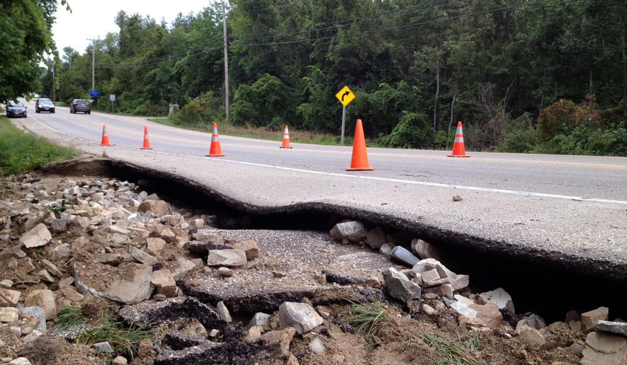 A road between Ephriam and Fish Creek, Wis., washed out by flash flooding from heavy rains is blocked off to traffic Friday, Sept. 5, 2014 on the Door County Penninsula. A utility spokesman said nearly 50,000 customers were without electricity at one point after storms and high wind toppled trees, utility poles and power lines. (AP Photo/Door County Advocate,  Samantha Hernandez)