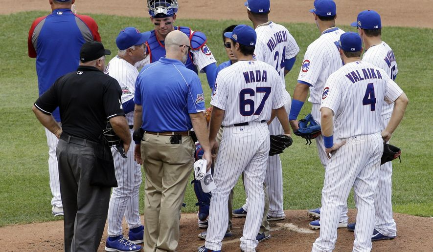 Chicago Cubs manager Rick Renteria, second from left, left, talks with starter Tsuyoshi Wada, of Japan, during the fourth inning of a baseball game against the Pittsburgh Pirates in Chicago, Friday, Sept.  5, 2014. (AP Photo/Nam Y. Huh)