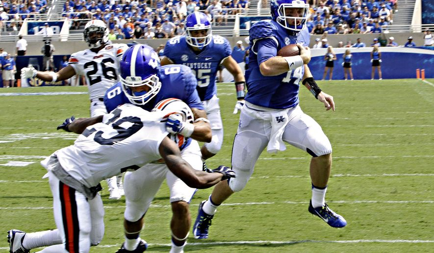 Kentucky quarterback Patrick Towles (14) sprints to the end zone to score a touchdown as teammate Blake Bone (56) blocks Tennessee-Martin's Aaron Simms (29)  in the second half of an NCAA college football game in Lexington, Ky., Saturday, Aug. 30, 2014.  (AP Photo/Garry Jones)