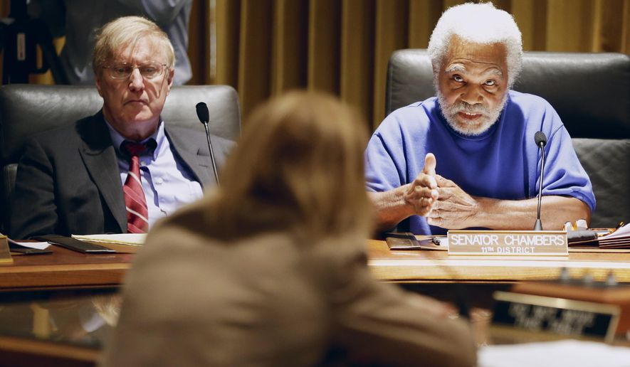 Neb. State Sen. Ernie Chambers, right, poses a question to former assistant attorney general Linda Willard, with State Sen. Paul Schumacher, left, during a committee hearing in Lincoln, Neb., Thursday, Sept. 4, 2014. Five state employees at the center of Nebraska's  prison scandal are scheduled to appear before a special legislative committee that's investigating why hundreds of sentences were miscalculated. (AP Photo/Nati Harnik)