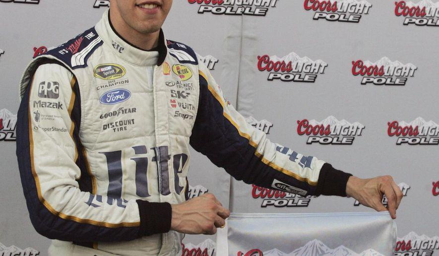 Brad Keselowski holds the pole award flag for winning the pole for Saturday's NASCAR Sprint Cup auto race at Richmond International Raceway in Richmond, Va., Friday, Sept. 5, 2014. (AP Photo/Jason Hirschfeld)