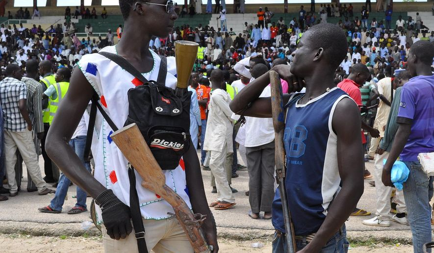 """Vigilante and local hunters armed with guns gather outside the Emir's palace in Maiduguri, Nigeria, Thursday, Sept. 4, 2014. The United States is preparing to launch a """"major"""" border security program to help Nigeria and its neighbors combat the increasing number and scope of attacks by Islamic extremists, a senior U.S. official for Africa said Thursday. Nigerian insurgents have begun attacking villages in neighboring Cameroon and have been seizing land in northeast Nigeria where they proclaimed an Islamic caliphate. (AP Photo/Jossy Ola)"""