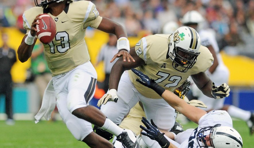 Central Florida QB Justin Holman breaks out of the pocket during the Croke Park Classic NCAA college football game in Dublin, Ireland, Saturday, Aug. 30, 2014. Penn State beat UCF, 26-24. (AP Photo/York Daily Record, Jason Plotkin)  YORK DISPATCH OUT