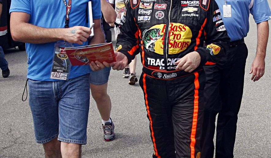 Driver Tony Stewart, right, signs an autograph for Shane Viatt, of Crawfordsville, Ind., after a practice session for Saturday night's NASCAR Sprint Cup series auto race at Richmond International Raceway, Friday Sept. 5, 2014, Richmond, Va.  (AP Photo/Richmond Times Dispatch, Bud Kraft)