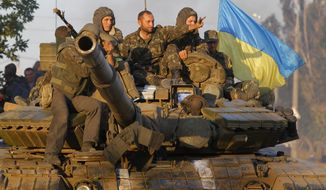 Soldiers of Ukrainian army ride on a tank in the port city of Mariupol, southeastern Ukraine, Friday, Sept. 5, 2014. The Ukrainian president declared a cease-fire Friday to end nearly five months of fighting in the nation's east after his representatives reached a deal with the Russian-backed rebels at peace talks in Minsk. (AP Photo/Sergei Grits)
