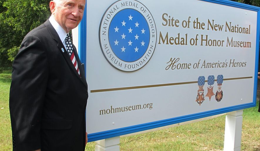 Billionaire businessman and former presidential candidate H. Ross Perot poses next to a sign designating the site of the future National Medal of Honor Museum at the Patriots Point Naval and Maritime Museum in Mount Pleasant, S.C. on Friday, Sept. 5, 2014. Perot visited to discuss plans for the $100 million museum. Organizers say he has donated millions to the effort but would not say specifically how much. Organizers hope to break ground next year.  (AP Photo/Bruce Smith)