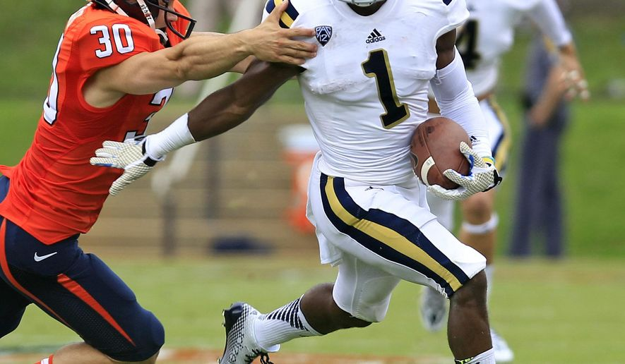 UCLA's Ishmael Adams (1) runs past Virginia place kicker Alec Vozenilek (30)  during the first half of an NCAA college football game at Scott Stadium, Saturday, Aug. 30, 2014, in Charlottesville, Va. (AP Photo/Andrew Shurtleff)