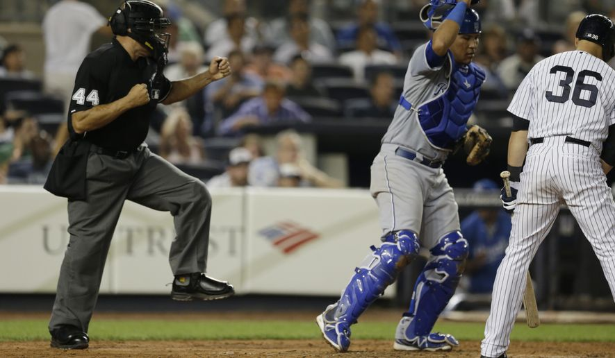 Home plate umpire Kerwin Danley, left, gestures as New York Yankees' Carlos Beltran (36) strikes out to end a baseball game in a 1-0 loss to the Kansas City Royals, Friday, Sept. 5, 2014, in New York. Royals catcher Salvador Perez, center, looks on. (AP Photo/Julio Cortez)