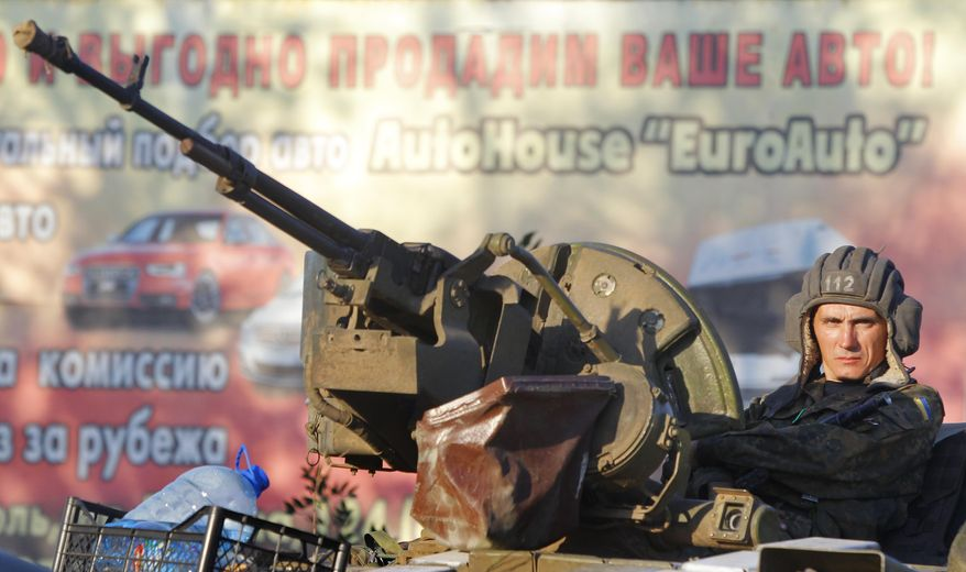 A soldier of the Ukrainian army sits on a tank in the port city of Mariupol, southeastern Ukraine, Friday, Sept. 5, 2014. The Ukrainian president declared a cease-fire Friday to end nearly five months of fighting in the nation's east after his representatives reached a deal with the Russian-backed rebels at peace talks in Minsk. (AP Photo/Sergei Grits)
