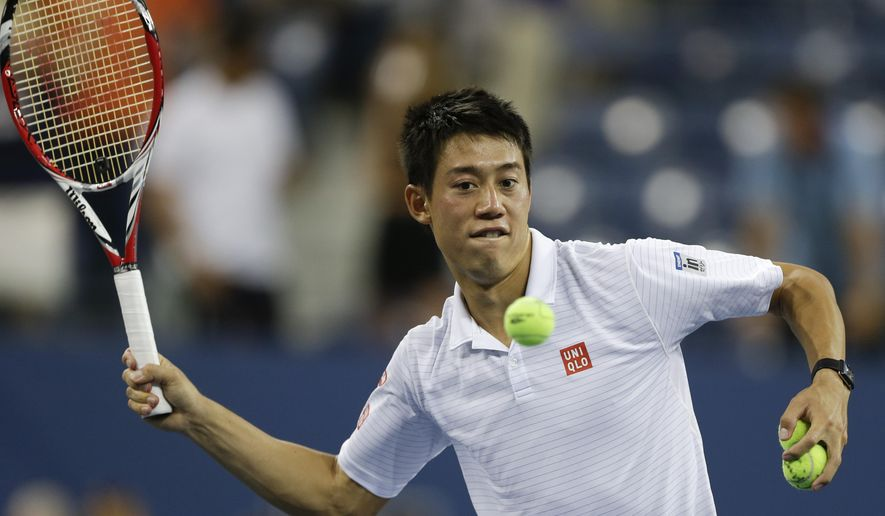 Kei Nishikori, of Japan, hits autographed balls into the crowd after defeating Stan Wawrinka, of Switzerland, in five sets during the quarterfinals of the 2014 U.S. Open tennis tournament, Wednesday, Sept. 3, 2014, in New York. (AP Photo/Darron Cummings)