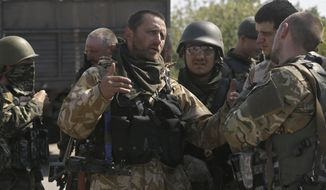 """Soldiers of special battalion """"Azov""""; talk at a checkpoint in the port city of Mariupol, southeastern Ukraine, Friday, Sept. 5, 2014. Shelling resounded on the outskirts of the city Friday as Russian-backed rebels pressed their offensive in the strategically key southeast just hours ahead of talks that are widely hoped to bring a cease-fire. Associated Press reporters heard heavy shelling on Friday morning north and east of Mariupol. (AP Photo/Sergei Grits)"""