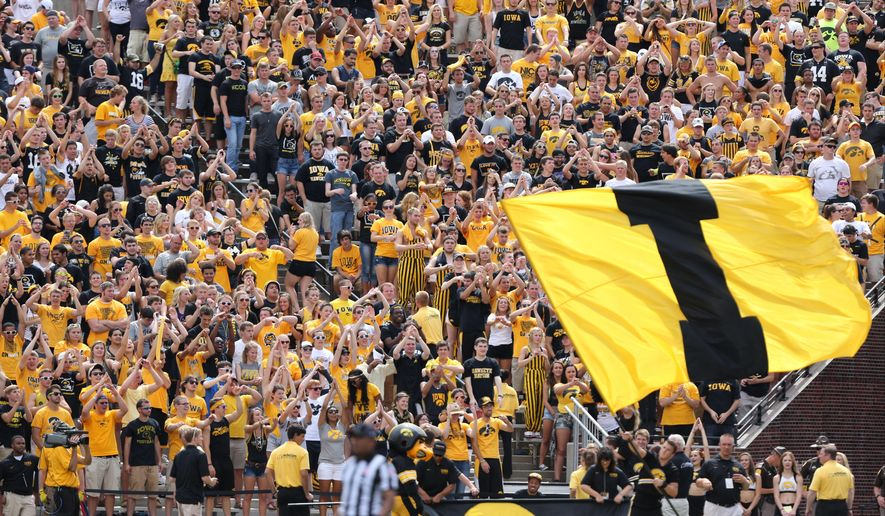 In this photo taken on Saturday, Aug. 30, 2014, the Iowa student section cheers during the second half of an NCAA college football game against Northern Iowa in Iowa City, Iowa. In an attempt to lure students to seats, the University of Iowa recently tried its most desperate promotion yet: A raffle for free tuition if a student purchased a book of season tickets. (AP Photo/Justin Hayworth)