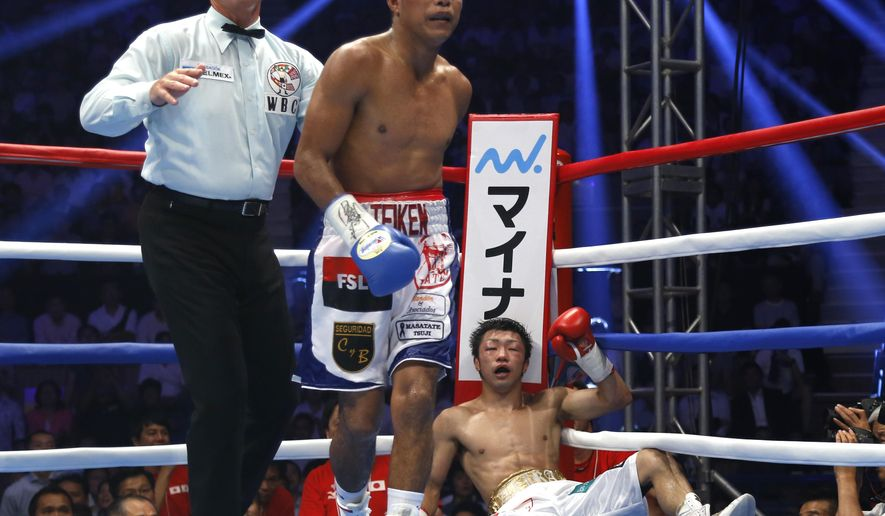 Nicaraguan challenger Roman Gonzalez returns to his corner after knocking down Japanese champion Akira Yaegashi, foreground, in the 10th round of their WBC flyweight boxing title match in Tokyo, Friday, Sept. 5, 2014. Gonzalez won the title after defeating Yaegashi by a technical knockout in the round. (AP Photo/Toru Takahashi)