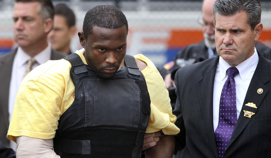 FILE - In this Oct. 25, 2012, file photo, Darrell Fuller is escorted out of a police station in Mineola, N.Y.  Fuller, who was convicted in July 2014 of killing a police officer during a traffic stop and then a motorist while he was fleeing was sentenced Friday, Sept. 5, 2014 to life in prison. (AP Photo/Seth Wenig, File)