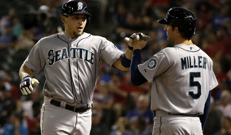 Seattle Mariners' Mike Zunino, left, is congratulated by Brad Miller (5) after hitting a solo home run off Texas Rangers' Scott Baker in the fifth inning of a baseball game, Friday, Sept. 5, 2014, in Arlington, Texas. Miller would go on to hit a two-run home run off Baker in the same inning. (AP Photo/Tony Gutierrez)