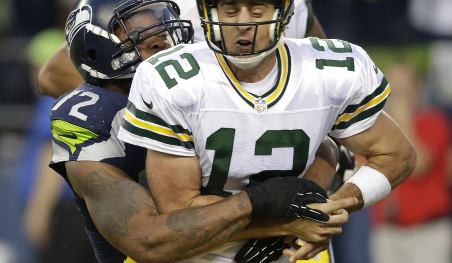 Seattle Seahawks defensive end Michael Bennett forces Green Bay Packers quarterback Aaron Rodgers to fumble in the second half of an NFL football game, Thursday, Sept. 4, 2014, in Seattle. A Packers player recovered the ball in the end zone, but was tackled for a safety on the play. (AP Photo/Scott Eklund)