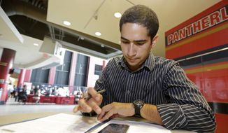 In this photo taken Tuesday, Aug. 19, 2014, Freddy Jerez, of Hollywood, Fla., fills out a job application during a job fair in Sunrise. Fla.  The government issues the August jobs report on Friday, Sept. 5, 2014. (AP Photo/Alan Diaz)