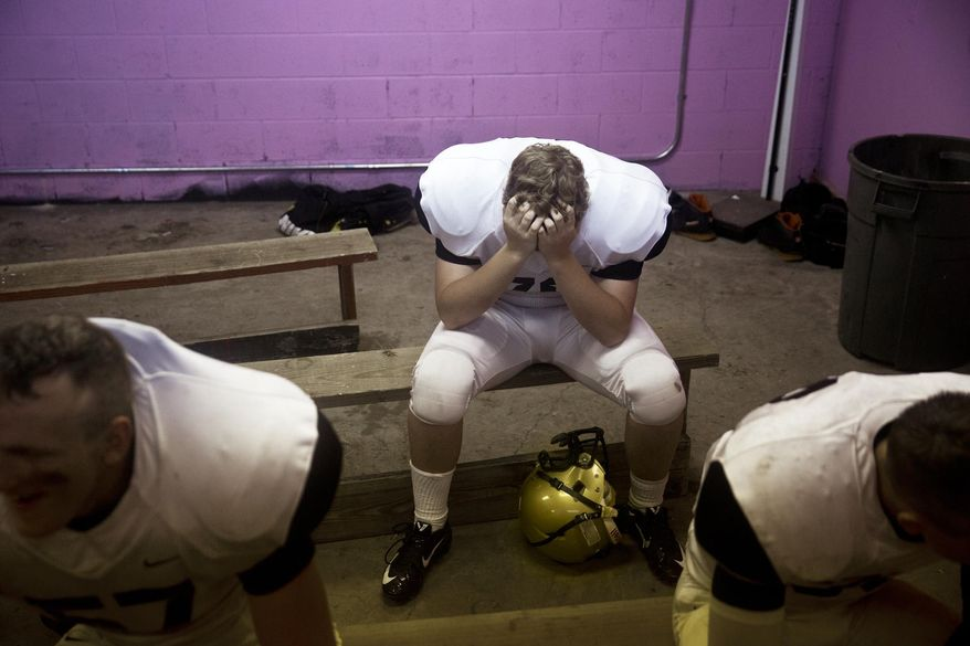 Corunna player Michael Oakes throws his hands over his face in exhaustion while waiting out a lightening delay in the visiting locker room in a game against Montrose Hill-McCloy High School at Montrose Hill-McCloy High School in Montrose on Friday, Sep. 5, 2014. The Rams led the Cavaliers at the half with a score of 14-7. The game has been postponed until tomorrow at 1 p.m. after a lightening delay. (AP Photo/The Flint Journal, Erin Kirkland)
