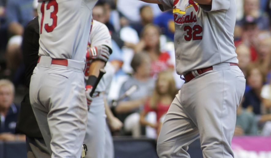 St. Louis Cardinals' Matt Adams, right, celebrates his two-run home run against the Milwaukee Brewers with Matt Carpenter, left, during the first inning of a baseball game Saturday, Sept. 6, 2014, in Milwaukee. (AP Photo/Darren Hauck)