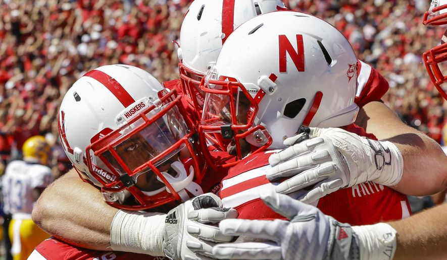 Nebraska quarterback Tommy Armstrong Jr., right, and offensive lineman Jake Cotton, center rear, celebrate with running back Ameer Abdullah, left, after Abdullah scored the winning touchdown against McNeese State in the second half of an NCAA college football game in Lincoln, Neb., Saturday, Sept. 6, 2014. Nebraska won 31-24. (AP Photo/Nati Harnik)