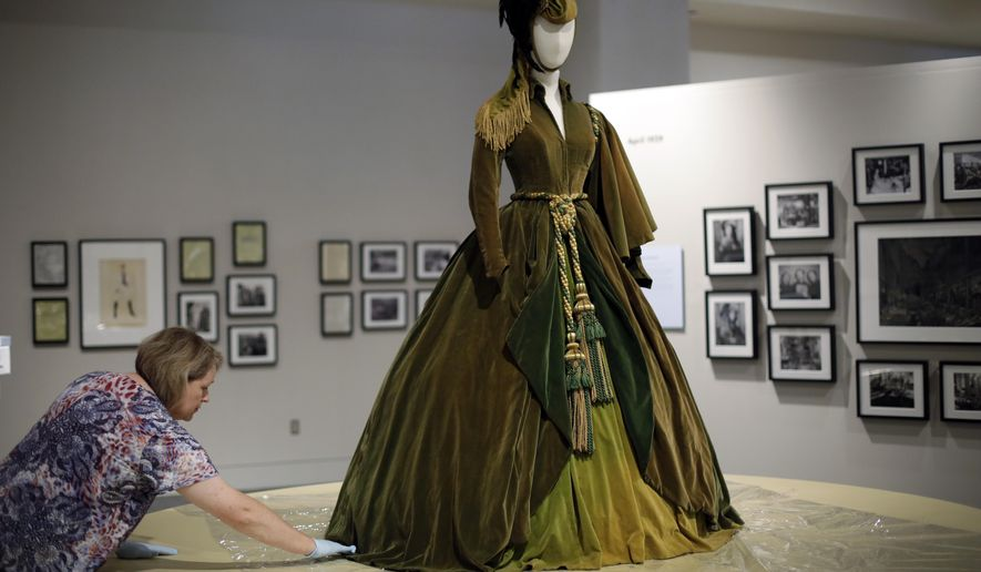 """In this Aug. 27, 2014 photo, conservator Mary Baughman helps prepare the green curtain dress from the movie """"Gone with the Wind"""" for display at the University of Texas' Harry Ransom Center in Austin, Texas. Beginning Tuesday, hundreds of items from the film will be on exhibit through Jan. 4, 2015, as part of a 75th anniversary tribute called """"The Making of Gone With the Wind."""" (AP Photo/Eric Gay)"""