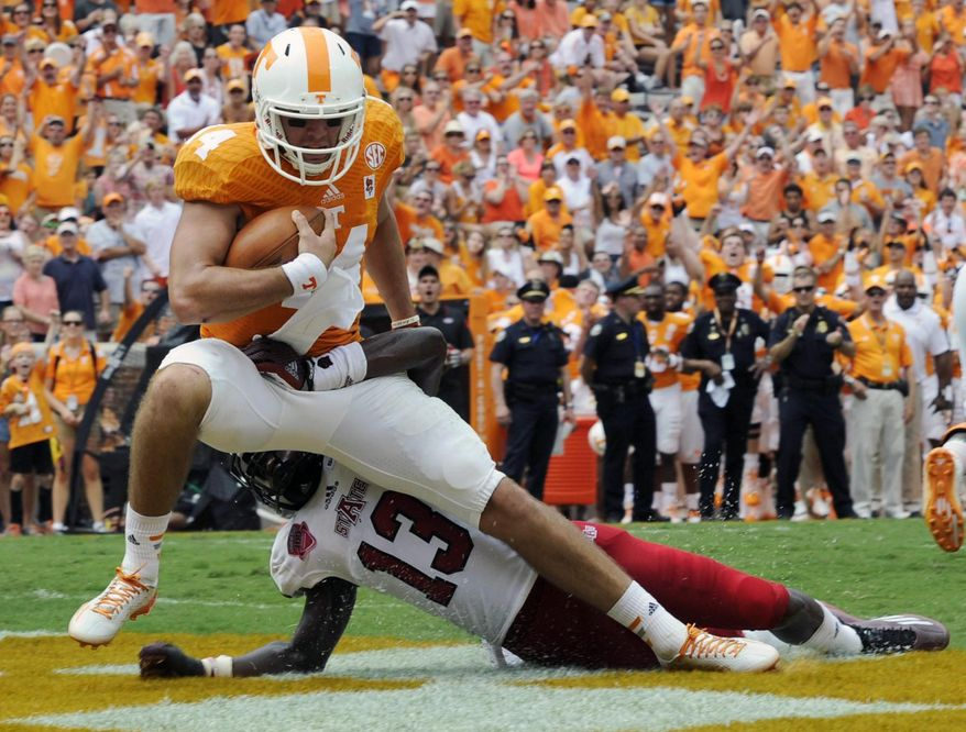Tennessee quarterback Justin Worley (14) drags Arkansas State defensive back Charleston Girley (13) as he runs for a touchdown during an NCAA college football game Saturday, Sept. 6, 2014, in Knoxville, Tenn.  (AP Photo/Knoxville News Sentinel, Amy Smotherman Burgess)