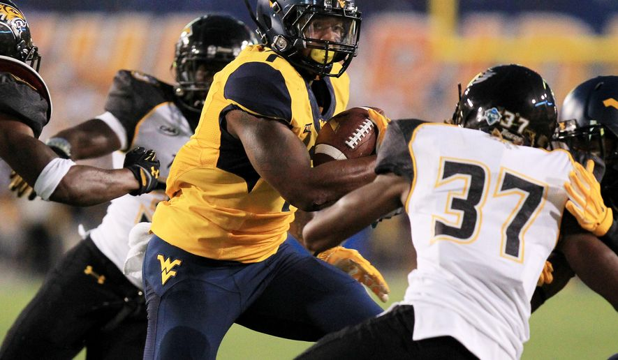 West Virginia running back Rushel Shell (7) carries the ball past Towson's Alfonso Augustine (37) during the first quarter of an NCAA college football game in Morgantown, W.Va., Saturday, Sept. 6, 2014. (AP Photo/Chris Jackson)