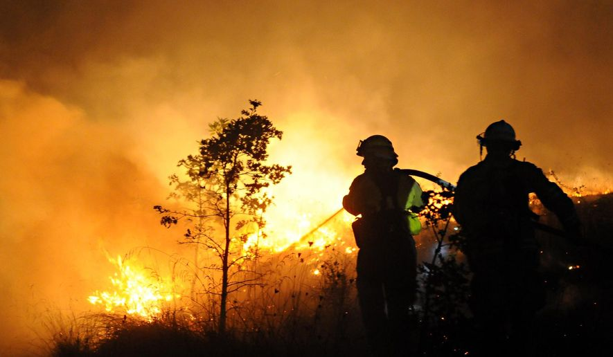 Firefighters from Alsea, Ore. douse flames on a Chip Ross Park Hillside in Corvallis, Ore. Friday Sept. 5, 2014. (AP Photo/The Corvallis Gazette-Times, Jesse Skoubo)