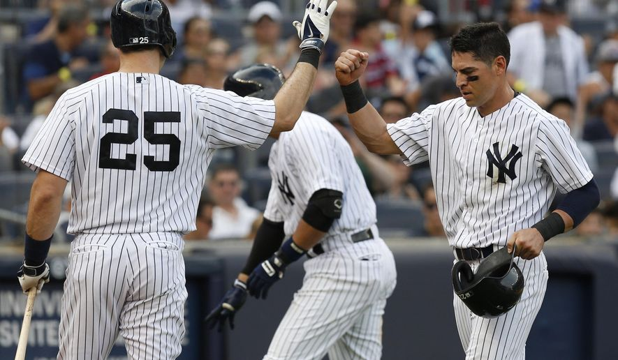 New York Yankees' Jacoby Ellsbury, right, is greeted by Mark Teixeira after scoring on a sacrifice fly during the third inning of the baseball game against the Kansas City Royals at Yankee Stadium, Saturday, Sept. 6, 2014 in New York. (AP Photo/Seth Wenig)
