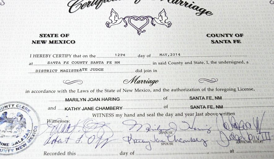 FILE - This photo taken on Monday, May 12, 2014, shows the certificate of marriage presented to Kathy Chambery, and her partner, Marilyn Haring of 23 years,  after they were married at Magistrate Court in Santa Fe, N.M.   More than half of marriage licenses issued from Santa Fe County in the last year have gone to same-sex couples. Data from the Santa Fe County Clerk's Office shows that the number of licenses given out doubled and 55 percent went to same-sex couples.  New Mexico became the 17th state to legalize same-sex marriage on Dec. 19, through a unanimous ruling by the state Supreme Court. (AP Photo/The Santa Fe New Mexican, Jane Phillips)