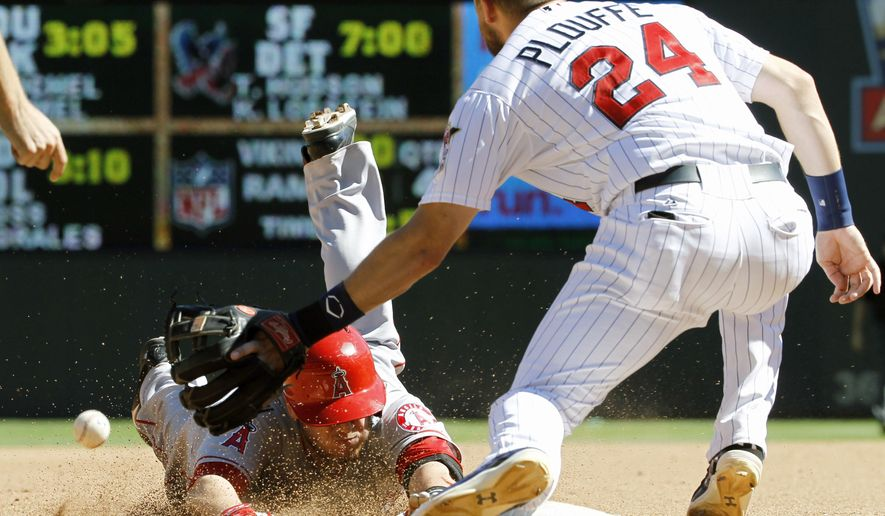 Los Angeles Angels' C.J. Cron, left, dives safely into third on an error by Minnesota Twins center fielder Aaron Hicks as Twins third baseman Trevor Plouffe (24) bobbles the throw from center field during the fifth inning of a baseball game in Minneapolis, Sunday, Sept. 7, 2014. (AP Photo/Ann Heisenfelt)