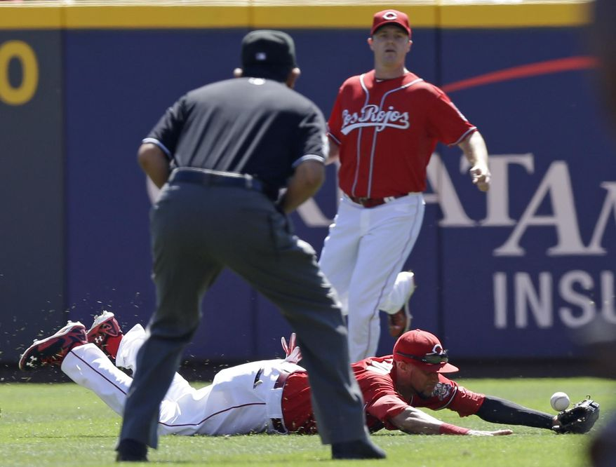 Cincinnati Reds center fielder Billy Hamilton dives between umpire Alfonso Marquez and right fielder Jay Bruce just missing a base hit by New York Mets' Kirk Nieuwenhuis in the first inning of a baseball game, Sunday, Sept. 7, 2014, in Cincinnati. (AP Photo/Al Behrman)