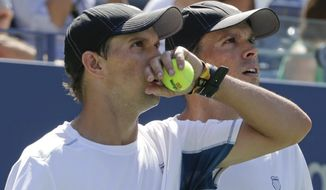 Mike, left, and Bob Bryan watch a replay on the screen during a semifinal doubles match against Scott Lipsky and Rajeev Ram at the 2014 U.S. Open tennis tournament, Thursday, Sept. 4, 2014, in New York. (AP Photo/Julio Cortez)