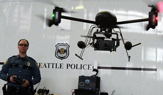 ** FILE ** In this April 27, 2012, file photo, Seattle Police officer Reuben Omelanchuk is at the controls of the department's new, small radio-controlled Draganflyer X6 drone with a camera attached in Seattle. Wyoming lawmakers are considering a bill to ban law enforcement use of drones without a warrant. (AP Photo/The Seattle Times, Alan Berner, File)