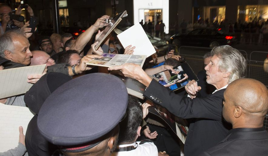 "Roger Waters, right, signs autographs as he arrives for the premiere of ""Roger Waters: The Wall"" at the Toronto International Film Festival in Toronto on Saturday, Sept. 6, 2014. (AP Photo/The Canadian Press, Frank Gunn)"