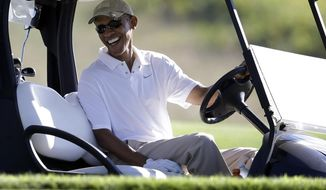 President Barack Obama smiles at the wheel of a golf cart during golfing at Vineyard Golf Club in Edgartown, Mass., on the island of Martha's Vineyard, on Aug. 20, 2014. (AP Photo/Steven Senne, File)