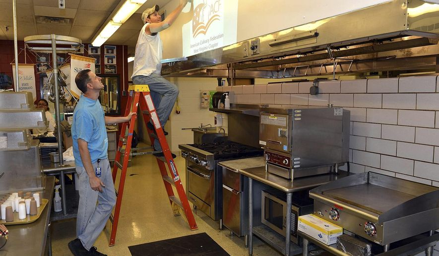 ADVANCE FOR RELEASE SUNDAY, SEPT. 7, 2014, AT 9:00 A.M. EDT. - This Aug. 29, 2014 photo shows Culinary Arts Program Director Thomas Grant, left,  watching Jared Oxley, 17, a senior at Sissonville High School, as he paints the kitchen at the Carver Cafe located in the Carver Career and Technical Education Center in Charleston, W.Va. But this lunch destination won't stay open for long. In fact, it will only be open on Wednesdays for just a couple short hours. (AP Photo/The Daily Mail, Craig Cunningham)
