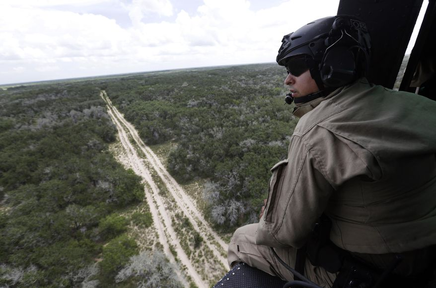A U.S. Customs and Border Protection Air and Marine agent peers out of the open door of a helicopter during a patrol flight near the Texas-Mexico border. (AP Photo)