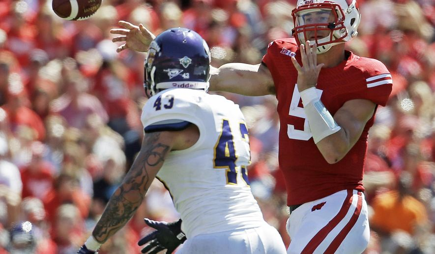 Wisconsin quarterback Tanner McEvoy throws past Western Illinois's J.J. Raffelson (43) during the second half of an NCAA college football game Saturday, Sept. 6, 2014, in Madison, Wis. Wisconsin won 37-3. (AP Photo/Morry Gash)