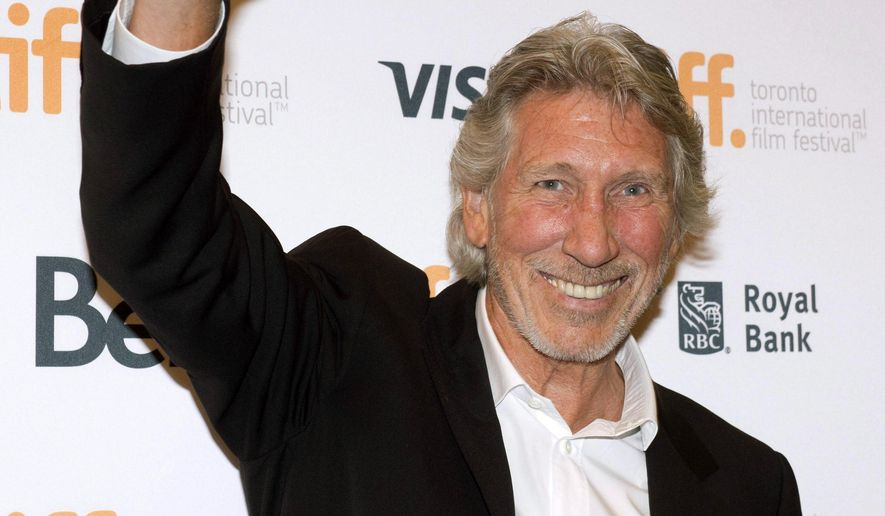 """Roger Waters waves as he arrives for the premiere of """"Roger Waters: The Wall"""" at the Toronto International Film Festival in Toronto on Saturday, Sept. 6, 2014. (AP Photo/The Canadian Press, Frank Gunn)"""