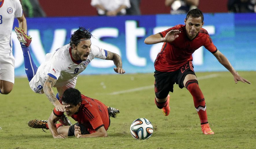 Chile's Mauricio Pinilla, top left, trips over Mexico's Miguel Herrera during the second half of an international friendly soccer match Saturday, Sept. 6, 2014, in Santa Clara, Calif. The game ended in a 0-0 draw. (AP Photo/Marcio Jose Sanchez)