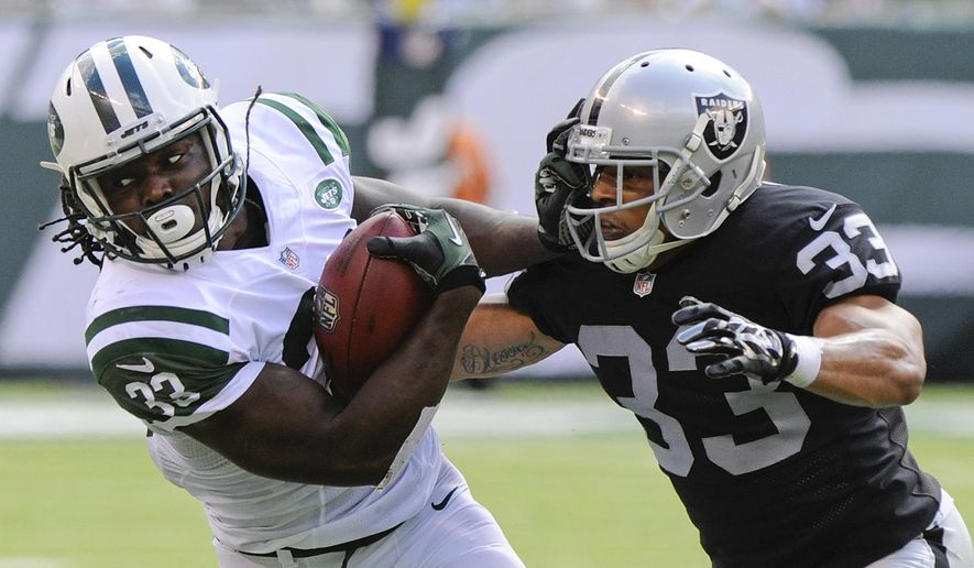 New York Jets running back Chris Ivory (33) stiff arms Oakland Raiders' Tyvon Branch (33) during the first half of an NFL football game Sunday, Sept. 7, 2014, in East Rutherford, N.J. (AP Photo/Bill Kostroun)