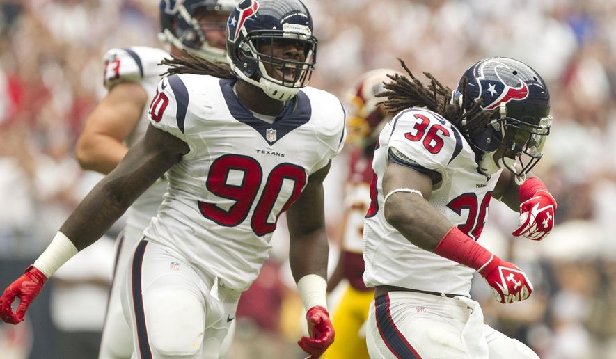 Houston Texans safety D.J. Swearinger (36) celebrates with outside linebacker Jadeveon Clowney (90) after sacking Washington Redskins quarterback Robert Griffin III (10) in the first half of an NFL football game Sunday, Sept. 7, 2014, in Houston. Houston defeated Washington 17-6. (AP Photo/ The Courier, Jason Fochtman)