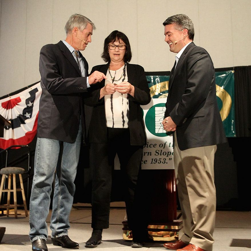 Moderator Rachel Richards flips a coin to start the Club 20 Debate as Senator Mark Udall (left) and Rep. Cory Gardner look on. The Udall campaign passed on requests for debates from two Denver TV stations. (Associated Press)