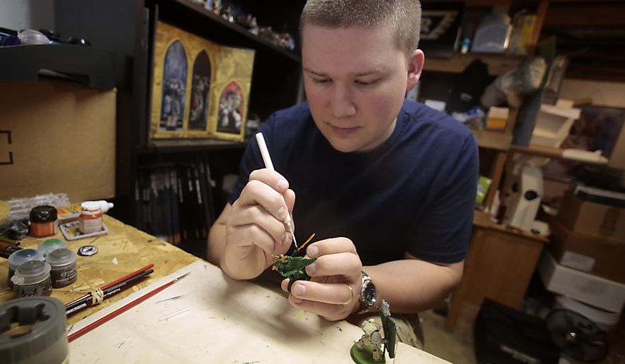 ADVANCE FOR SUNDAY  SEPT. 7 - In this May 23, 2014 photo,Thomas Severson hand paints one of his thousands of Warhammer 40,000 miniatures in Dubuque, Iowa. Severson competes in tournaments using the miniatures. Severson owns over 2,000 miniatures, all of which he has or plans to hand paint himself. (AP Photo/The Telegraph Herald, Brian Achenbach)
