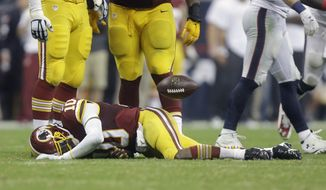 Washington Redskins' Robert Griffin III (10) lies on the turf after he was sacked for a loss by Houston Texans' J.J. Watt during the third quarter of an NFL football game against the Washington Redskins, Sunday, Sept. 7, 2014, in Houston. (AP Photo/Patric Schneider)